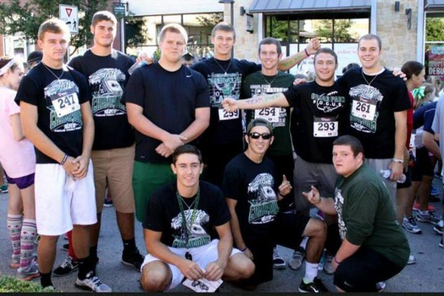 Members+of+the+varsity+football+team+cheer+on+honorary+Timberwolf%2C+Joshua+Edmondson+during+the+Champions4Children+marathon+on+Sept.+23.+Photo+courtesy+of+The+Support+Joshua+facebook+page.