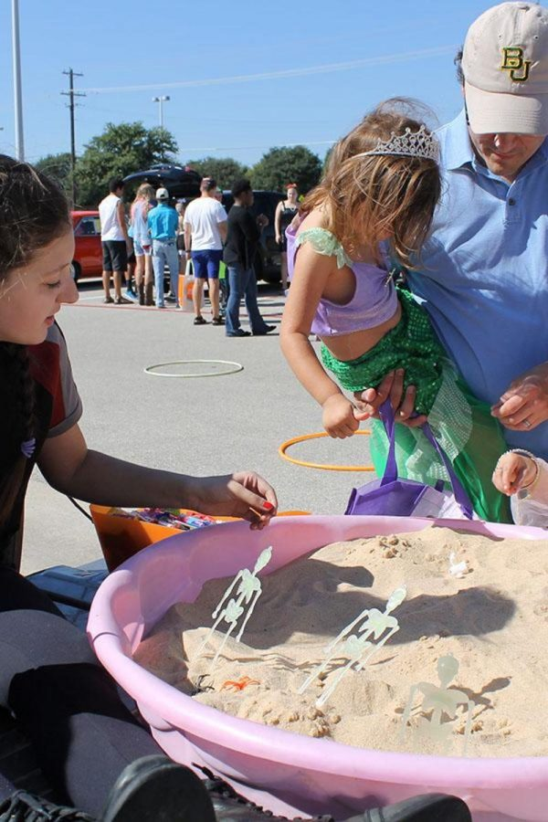 Sophomore+Lindsey+Foster+helps+young+kids+work+with+the+sand+pit.%0ASpanish+Club+is+one+of+the+clubs+that+participated+in+Trunk+or+Treat+and+they+had+a+sand+pit+that+kids+could+dig+through+and+find+little+treasures.+%0A%22The+children+and+their+costumes+are+my+favorite+part+because+they+are+adorable%2C%22+Ayah+Alomari+said.+%22It+truly+makes+your+day.%22