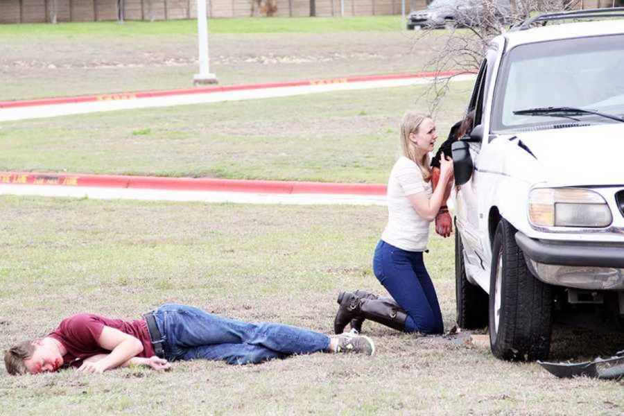 In despair, senior Lexi Breed clutches the arm of Shattered Dreams victim senior Reagan Head during the crash scene on March 12. Senior John Tolander (left) and Biology teacher Brent Grissom (not pictured) were also killed.
