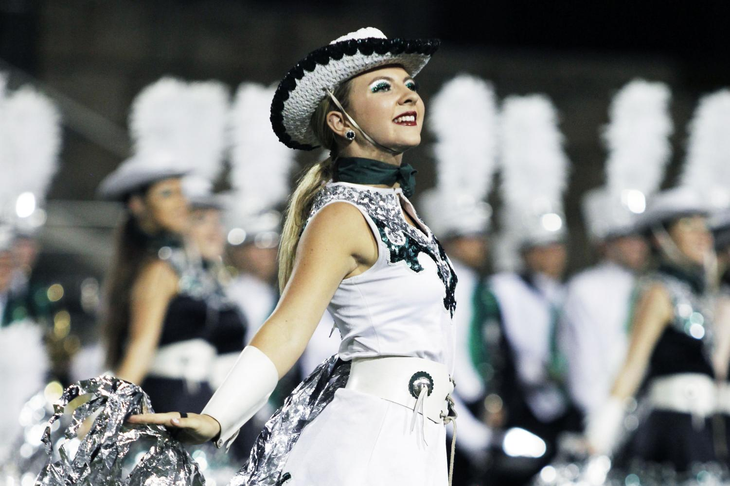"""Junior Lacey Hurley smiles proudly at the Cedar Ridge football game while performing with the celebrities. Hurley decided to graduate early this year after discovering that she only needed three more credits to qualify. """"I decided to graduate early just because I really felt like it was something that had been on my heart for a while,"""" Hurley said. """"And it was just something that I was really called to and I was just excited."""""""