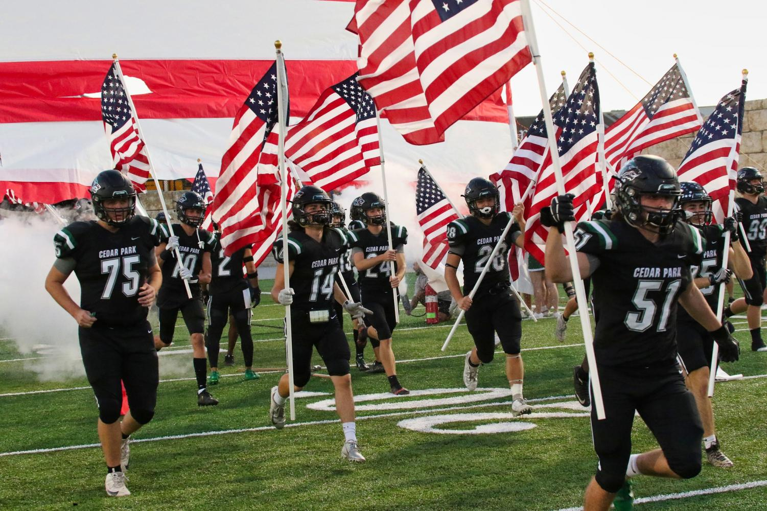 Showing their American Pride, CPFB enters the field before their match up against Hutto on Oct. 20. The Wolves beat the hippos 20-16 in a close game.