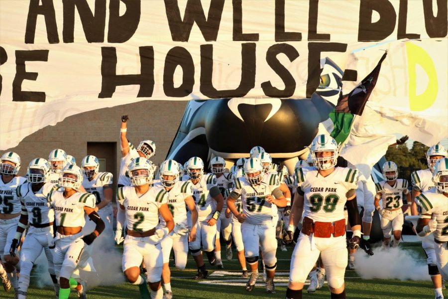 Cedar+Park%27s+varsity+boys+football+team+emerges+from+their+bust-out+before+facing+Rouse+on+Sept.+27.++The+importance+of+playing+with+total+effort+during+practice+and+games+is+emphasized+through+the+weekly+earning+of+the+leather+belt.+%22Whoever+gets+the+most+turnovers+within+the+week+during+practice%2C+that+person+gets+to+wear+the+belt+before+the+game%2C%22+senior+DE+Ben+Bell+said.+