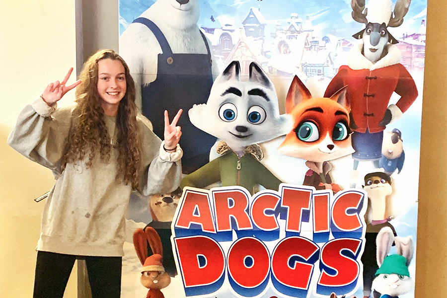 Holding+up+a+double+peace+sign%2C+Lacie+poses+next+to+the+movie+poster+for+the+new+animated+picture%2C+%E2%80%9CArctic+Dogs.%E2%80%9D