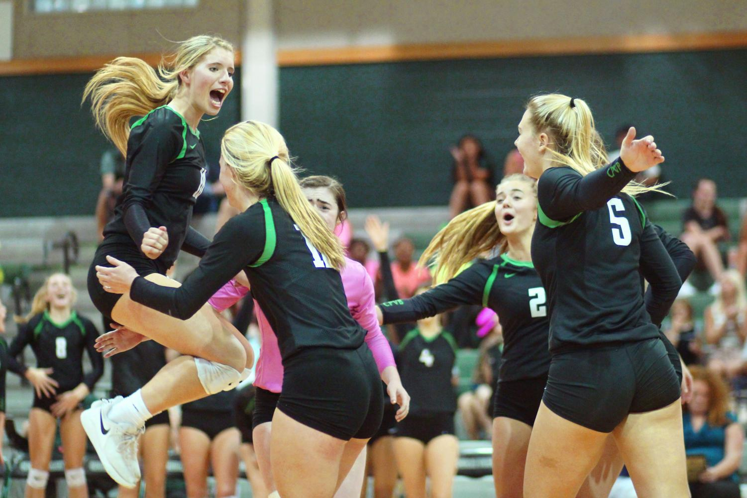 Jumping for joy, the volleyball team celebrates scoring. Wins like these are what propelled the team to Regional Semifinals.