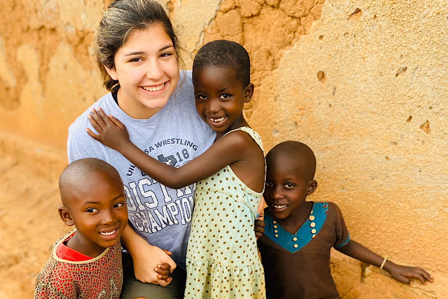 Senior+Faith+Elliott+smiles+along+with+three+Rwandan+children+in+the+village+of++Kageyo%2C+Rwanda.+Elliott+volunteers+with+a+group+called+Africa+New+Life+in+Rwanda+and+said+that+the+trip+impacts+her+every+year.+%22What+surprises+me+the+most+about+the+people+there+is+how+the+Rwandans+can+have+so+little+and+still+be+filled+with+joy.+This+year+was+different+than+the+last+because+I+already+knew+what+to+expect+and+saw+a+lot+of+old+friends+there%2C+it+was+like+I+was+going+back+home.%E2%80%9D%0A
