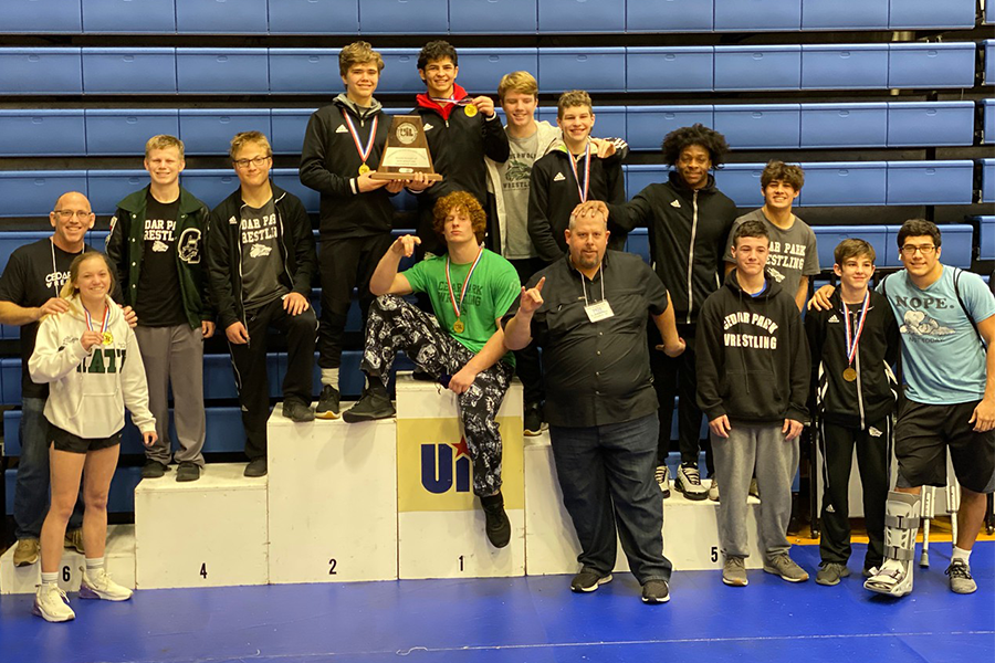 """The CPHS state wrestling team takes a photo following regionals. Five of the wrestlers placed in the tournaments, with senior Ben Bell winning the state title. """"It feels great to finish the year with a state championship,"""" Bell said."""