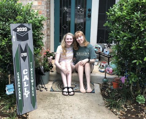 "Sophomore Lexi Hall and Senior Cally hall show off their newly painted door. ""As far as creativity goes, I feel like it has helped me enjoy my time in quarantine because I get to spend time doing things I like to do like drawing and painting that I usually don't have much time for with school"" Cally said."