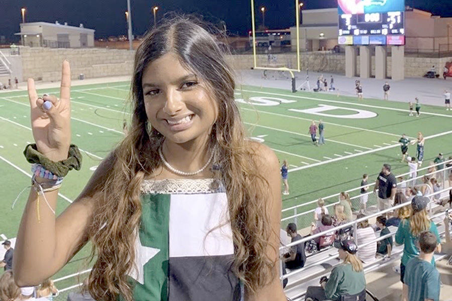 Holding+up+a+Timberwolf%2C+senior+Romeela+Kar+shows+her+school+spirit+during+the+homecoming+game+against+Cinco+Ranch.+Kar+said+she+has+never+missed+a+football+game+during+her+senior+year+of+high+school+due+to+her+being+a+dance+and+cheer+manager+and+being+the+football+teams%E2%80%99+photographer.+%E2%80%9CI+love+CP+football+because+of+how+it+brings+our+entire+community+together%2C%E2%80%9D+Kar+said.+%E2%80%9CNights+like+the+spring+game+are+my+favorite+because+the+entire+community+comes+out+to+support+the+T-Wolves.%E2%80%9D