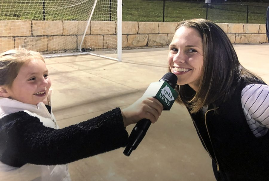 As her daughter, Aven Powell, pretends to be a CPHS News Reporter, AP Mitzi Powell smiles on the sidelines of Gupton Stadium in 2019. After three and a half years as assistant principal at CPHS, Powell is leaving to take the job as the district's Career Development Coordinator.
