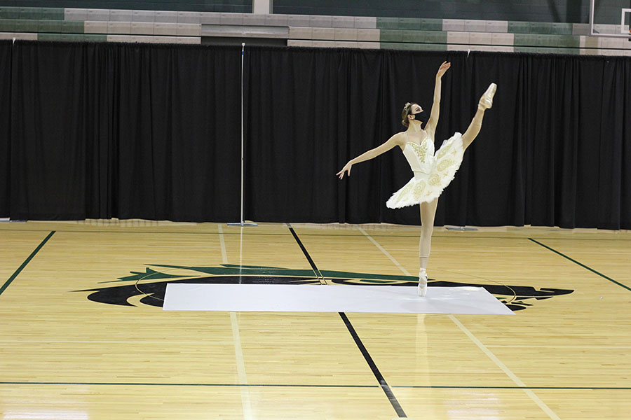 Looking to the side, senior Sydney Poulsen extends her leg while en pointe at the Celebrities holiday show on Dec. 13. This performance was the first time Poulsen had performed while en pointe in two years.