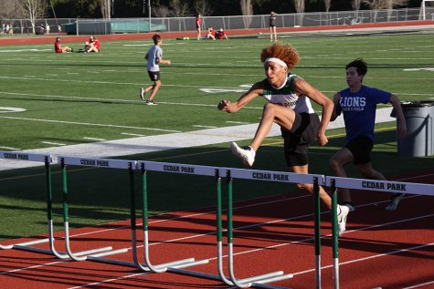 Looking ahead, junior Nick Grullon runs the hurdles at the track meet on Feb. 3. Due to Coronavirus.  the  amount of teams allowed at the meet were restricted, however the new changes don