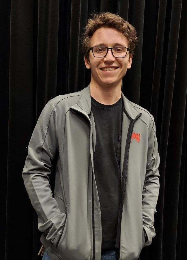 New Theatre Tech teacher Colin Falk faces the camera smiling while wearing his Disney Fantasmic Cast and Crew Jacket. Falk is an alumnus of Cedar Park High School who used to work for Disney