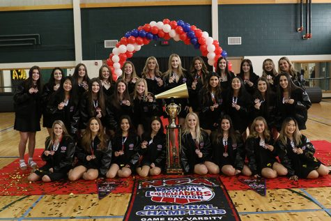 "Next to the NCA trophy, the varsity cheer squad shows off their medals and NCA jackets. The team competed in the Game Day category against teams all over the country, ultimately placing first.  ""We felt so rewarded and happy that we finally had our reward for winning,"" senior captain Sofia Attaguile said."