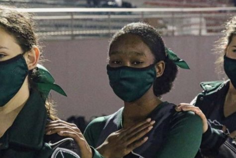 """Senior Keyona Williams, poses for a picture with two of her fellow cheerleaders. Due to COVID-19 restrictions cheerleaders were required to maintain a distance as well as wear masks. """"Cheering this year was fantastic,"""" Williams said. """"I really enjoyed our routines and getting to know the other girls on the team. I"""