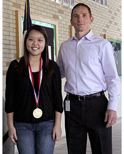 Eunice Lee, next to Principal John Sloan, has recently been recognized as an outstanding performer.