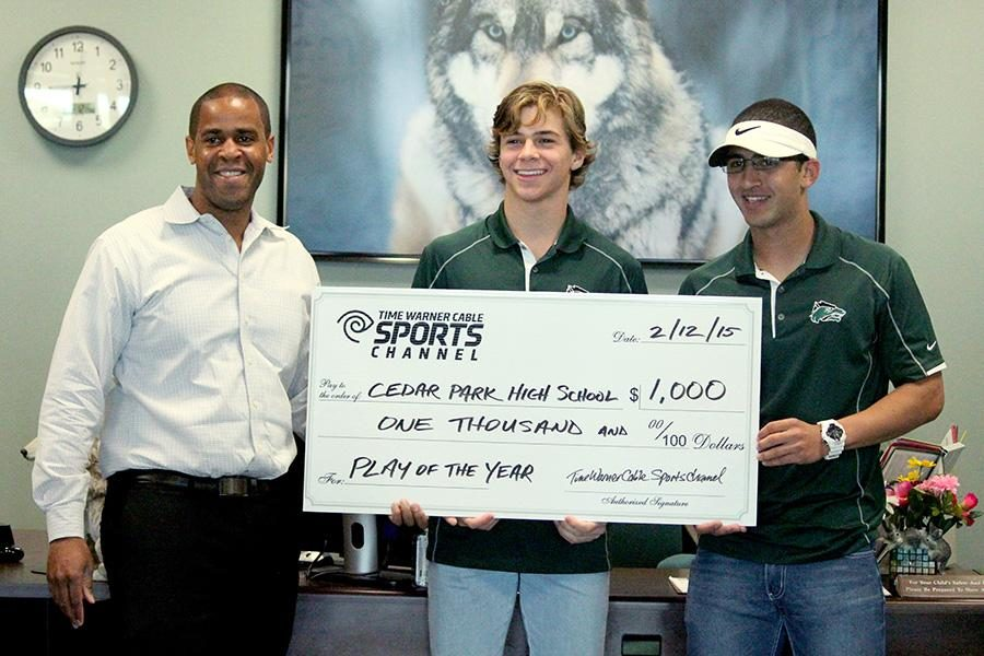 A Time Warner Cable rep presents junior Tommy Lavine and senior Amir Alzer with a $1000 check on Feb. 12 for winning the
