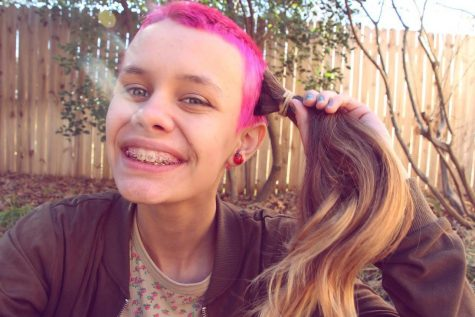 Sophomore Deana Trautz holds up her cut brown hair to her freshly dyed pink buzz cut.