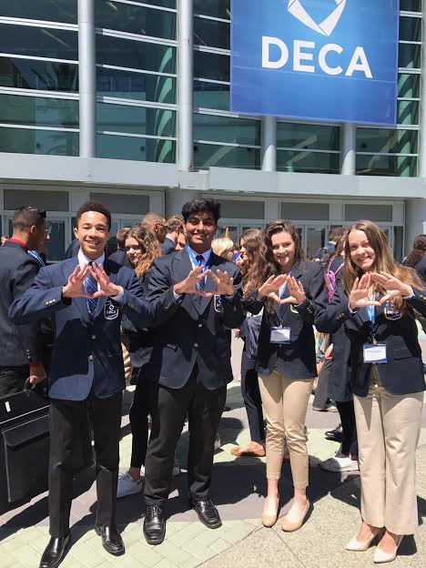 (left to right) junior Gregory Phea, seniors Sagar Kansara, Avery Daniel, Brittany Ballou. Holding up the DECA sign, DECA are dressed up before the award ceremony.