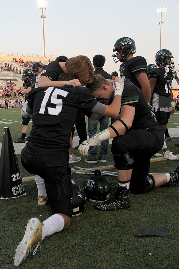 Seniors+Dalton+Hayek%2C+Mason+Brooks%2C+and+Allen+Grones+pray+together+before+the+first+football+game+of+the+season+Sept.+1.