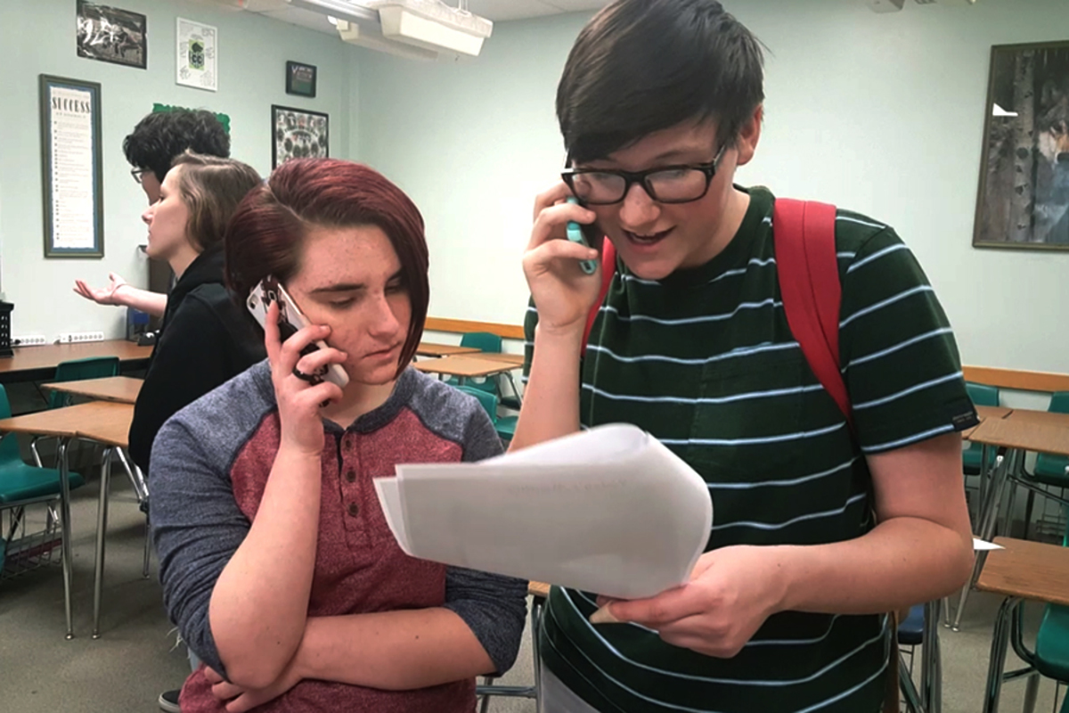 Reading off of a short script, freshman Peyton Fehrenbach and junior Kaitlin Cantwell call their representative. They were some of the 20 GSA members who called about immigration on Jan. 9 in AW109.