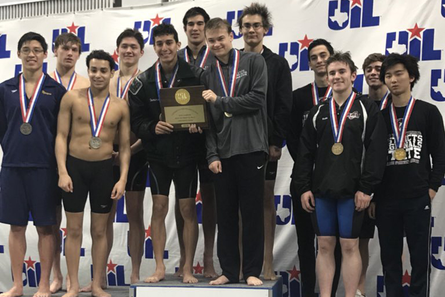 Vladimir Ivanov and the boys 200 yard freestyle relay team stand atop the first place podium and hold their state trophy.