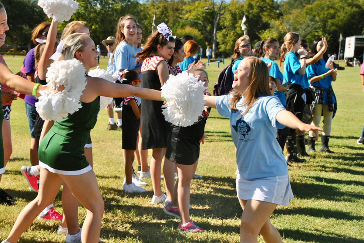 Greeting the other cheerleaders, senior Jordan Hagemann participates in the the   Buddy Walk hosted by the Down Syndrome of Central Texas. Hagemann is an ambassador with the association.