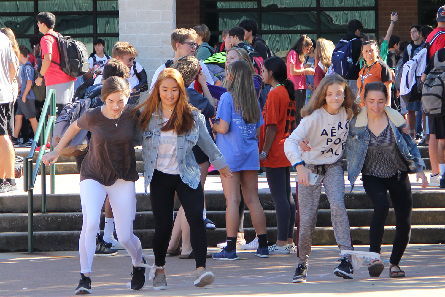 Running in a three-legged race, students participate in the Oct. 10 PACKtivity in the courtyard.