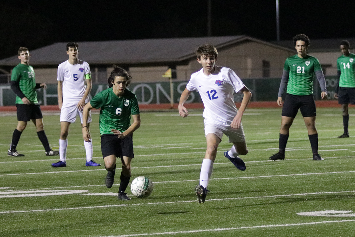 Junior left midfielder Michael Ernand attempts to juke out a defender in their season opener against Leander.