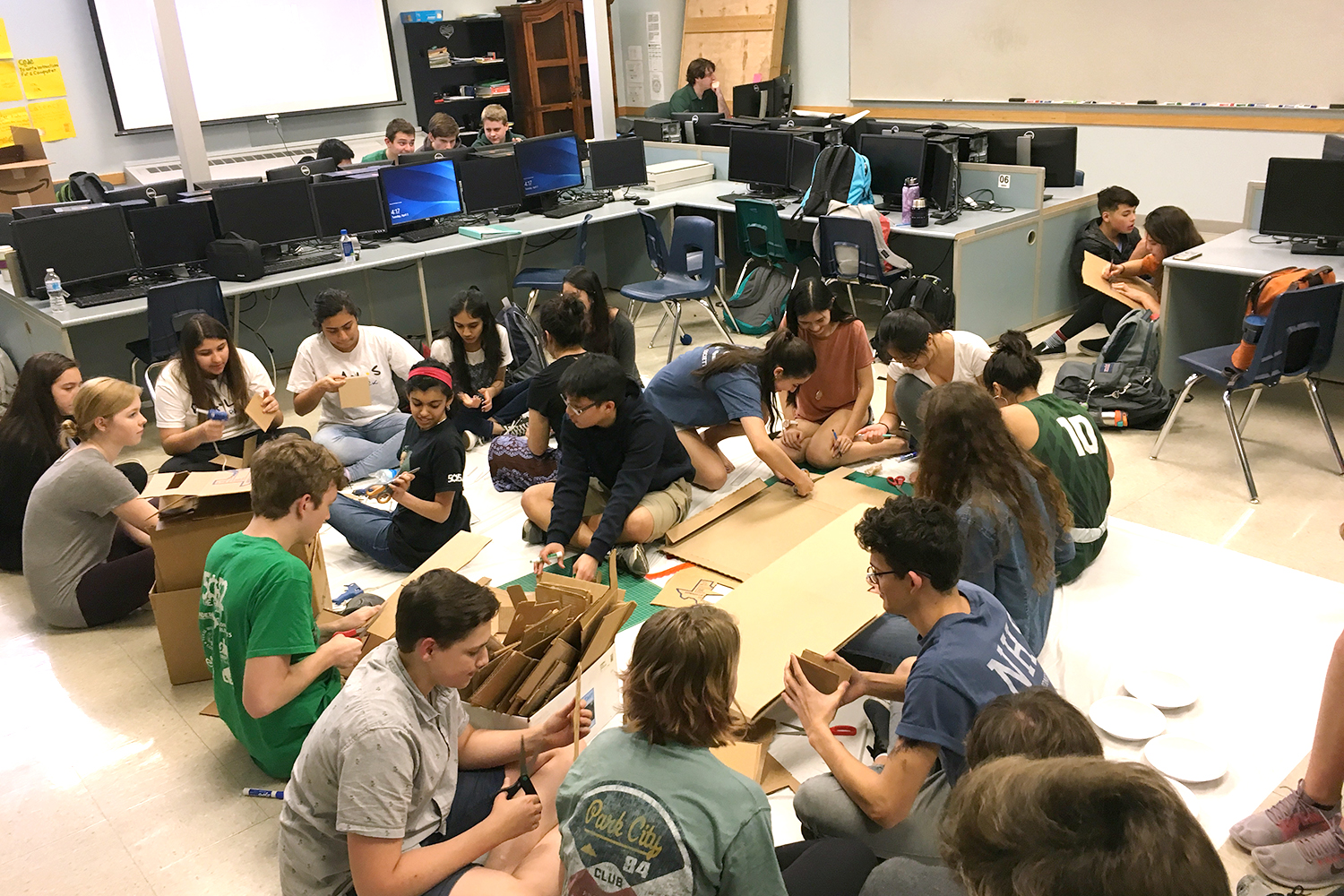 By cutting and gluing cardboard, and painting them green, students help make battery trash cans on April 3, 2018 in EIT.