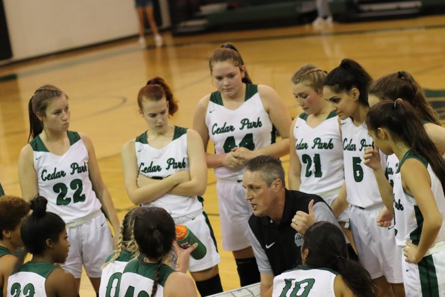 """Donny Ott, head coach of the girls basketball team, prepares the varsity team before a game. Ott became the head coach almost three years ago and said that in his years of coaching, Cedar Park has proven to be a school full of dedicated students.  """"The kids are amazing,"""" Ott said. """"I think that there is such a high expectation to be great at everything at Cedar Park."""