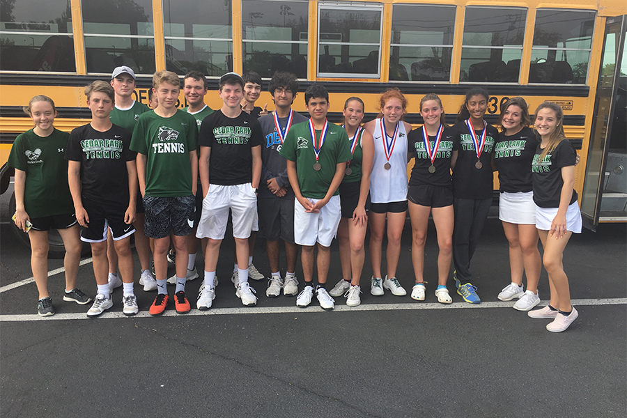 "The JV tennis team poses with their district medals. ""When I got first, I was surprised and happy knowing that my hard work had paid off,"