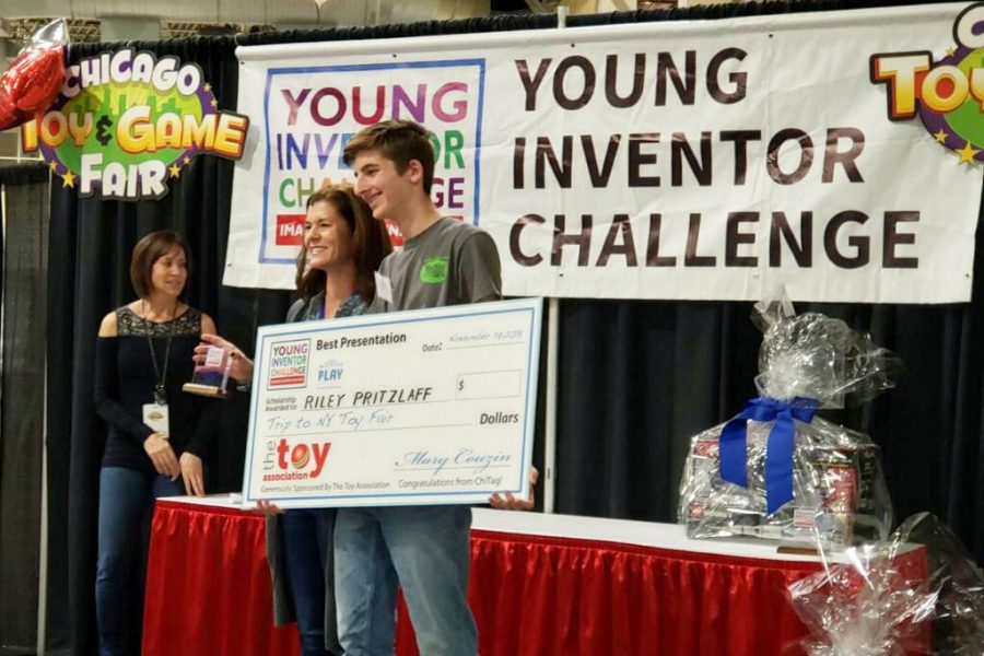 Getting+the+gold%2C+sophomore+Riley+Pritzlaff+is+presented+with+a+check+that+he+won+from+the+Young+Inventors+Challenge.+%22I+was+super+excited%2C+especially+after+the+hard+work+that+went+into+making+it+happen%2C%22+Pritzlaff+said.+%22It+was+sort+of+a+confirmation+that+I+had+done+something+really+special.%22