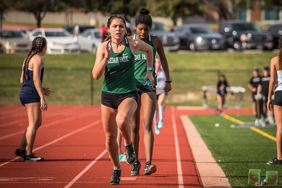 """Taking control of the baton, senior Alena Albertson leads a race at Rouse High School. Albertson has been in track for three years, and said she believed her teammates were a big motivation for helping her pursue her dream. """"Achieving my dream was hard, it came with a lot of ups and downs,"""" Albertson said. """"Waking up at 5 a.m. for hard practices, then pushing myself to run more after school was super hard, but having my teammates along the way pushing me to be the best I could be was what made it worth it."""""""