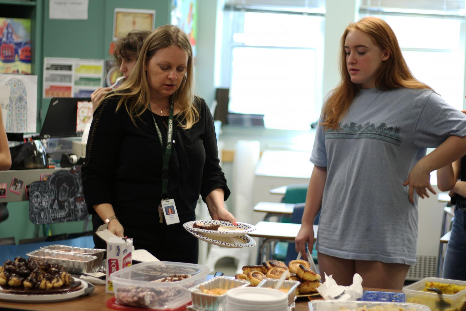 French teacher, Tammy Nettles and freshman Meredith Jenkins hover over the selection of courses, as Nettles instructs the class. Jenkins baked the palmiers and said that a part from getting the baking time right, the process of making them was easy.