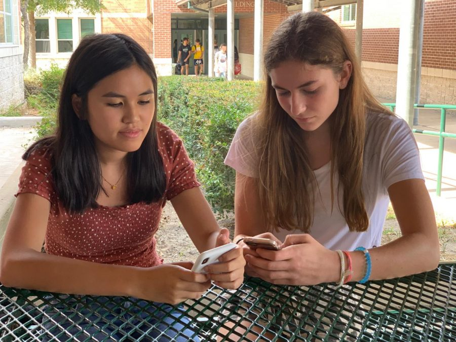 """Playing on their phones, sophomores Vy Dao and Jillian Lach demonstrate how phones can often be a distraction from face to face interactions. Broadcast teacher Anthony Garcia said that he believes social media has had a major impact on personal relationships. """"I think our society is being affected by this digital age in the way that we don't see each other as people anymore,"""" Garcia said."""