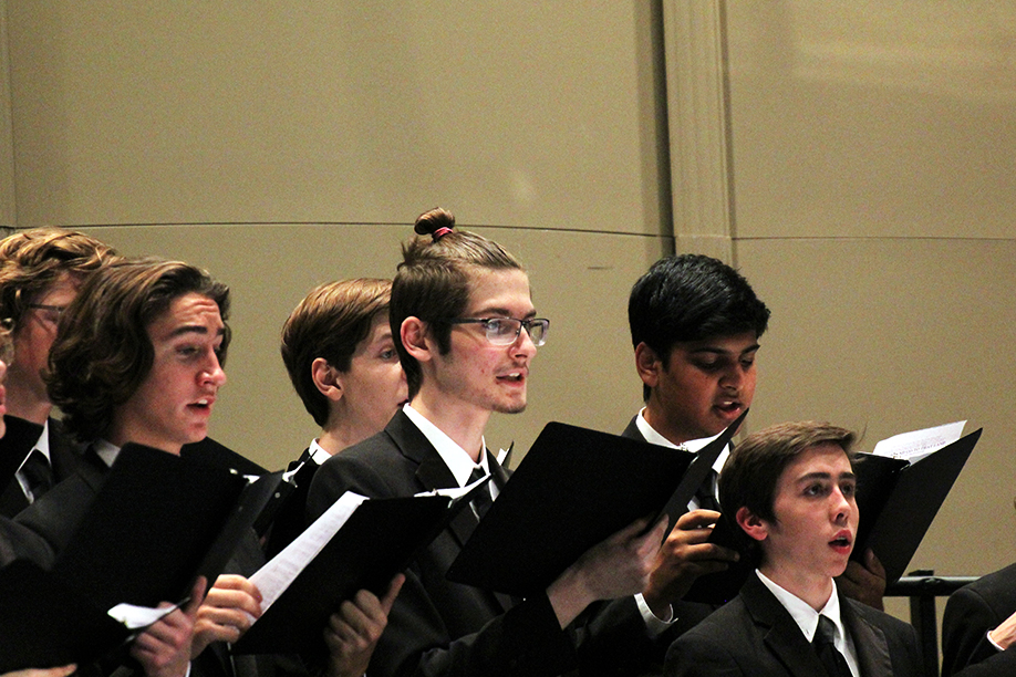 """Junior choir student Zain Jabbar (third from left to right) sings in the fall concert. The varsity mixed choir had prepared extensively for their TMEA performance, dedicating every minute to preparation. Jabbar reflects on this work. """"For four months, every Wednesday after school, we practiced for an hour and fifteen minutes on the four songs,"""" Jabbar says. """"And these weren't easy songs. Ms Holt made sure we chose really hard songs that the professional choirs do. I was really happy that all the hard work was recognized."""""""