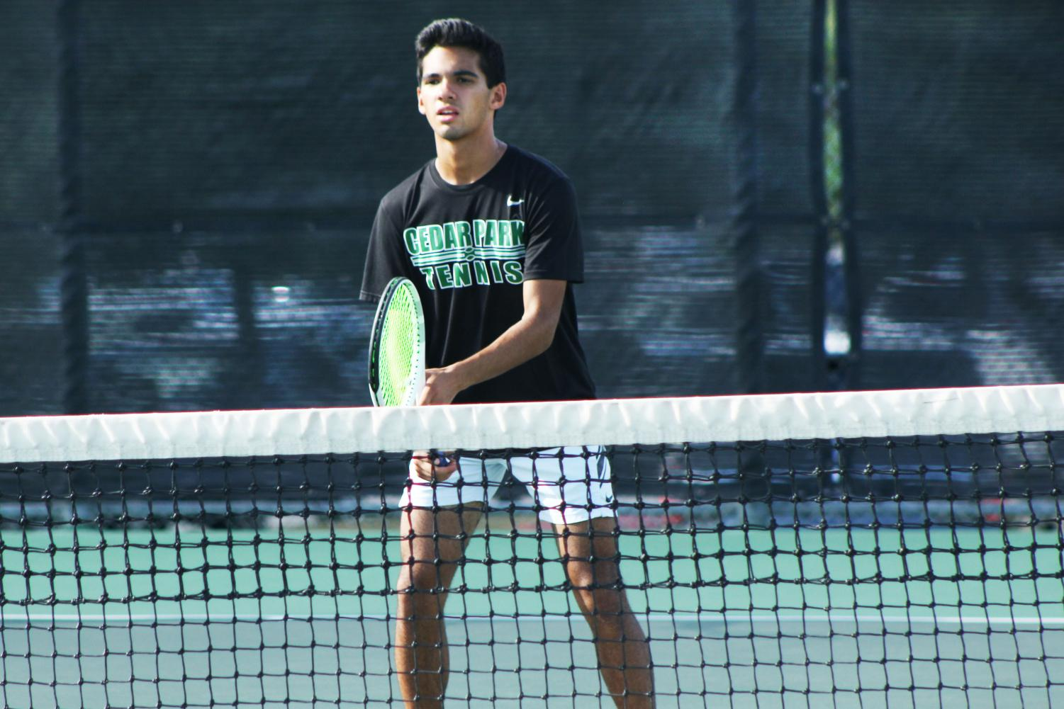 Senior varsity tennis player Bryce Bailey gets ready to return a serve during a match on Sept. 24. The varsity team has played a total of 15 matches and won every one, making them undefeated.