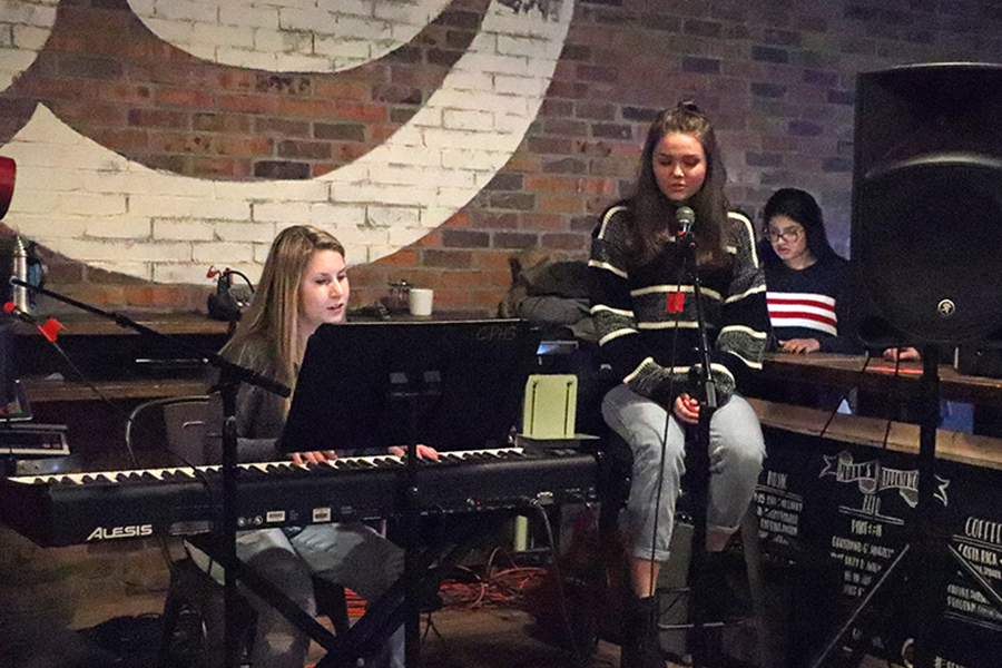 Sitting+on+a+stool%2C+freshman+Sophie+Dawson+sings+at+the+choir+coffee+house+showcase+on+Nov.+13.+Her+constant+practice+of+her+art+contributes+to+her+improvement+vocally+in+and+out+of+the+school+choir.+%E2%80%9CI+play+my+keyboard+at+night+after+I+get+done+with+everything+and+create+songs+off+the+top+of+my+head+for+fun%2C%E2%80%9D+Dawson+said.+