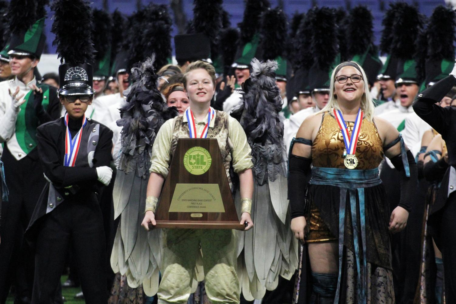 Surrounded by her fellow band members, sophomore Kierstyn Born holds the UIL state championship trophy. Born played Icarus in this year's show. She said that although she was nervous leading up to finals, afterwards she felt confident in their performance.