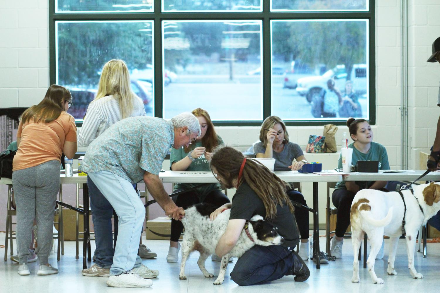 """A dog and his owner discuss the vaccine process during the Celebrities Pet Clinic on Nov. 6. The dance team, with help from parent volunteers, held their annual clinic at Cedar Park this year and served pet owners from all over the community.""""My favorite part about helping out was seeing the Celebrities in action as they pretty much ran the whole event,"""" volunteer and parent Kelly Richardson said. """"Dr. and Mrs. Tarlton even commented about how helpful and professional our girls were, and they work with lots of organizations to do these clinics."""""""