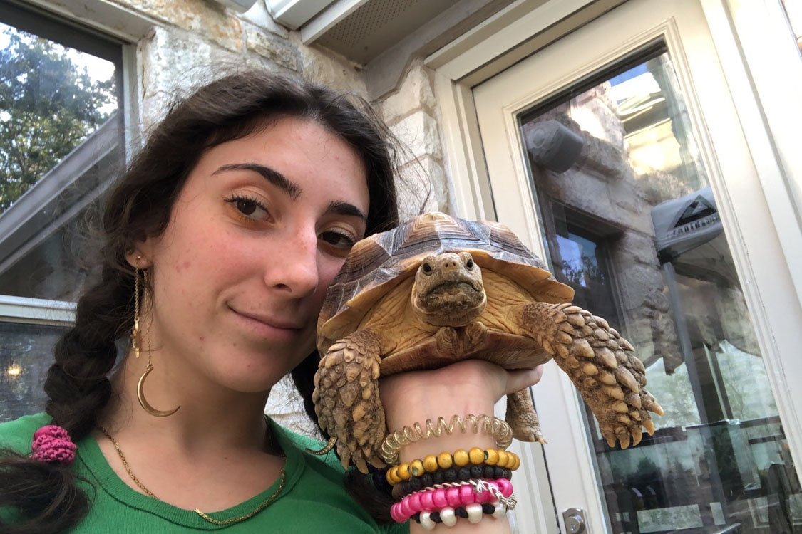 """Senior Natalia Peck takes a picture with her pet tortoise, Jenga. According to Peck, animals have always been a love of hers, and she cannot recall ever wanting a job that did not deal with animals, and is currently working in reptile husbandry at the Austin Aquarium. """"I have wanted to work at the aquarium since I was thirteen,"""" Peck said. """"I wasn't old enough to work there until I was sixteen last year. I met a really good friend of mine who was working there, and she took me to my first interview there. I wouldn't have been brave enough to get that job on my own. I work in reptile husbandry, so I take care of the cold blooded reptiles, which are one of my favorite things ever."""