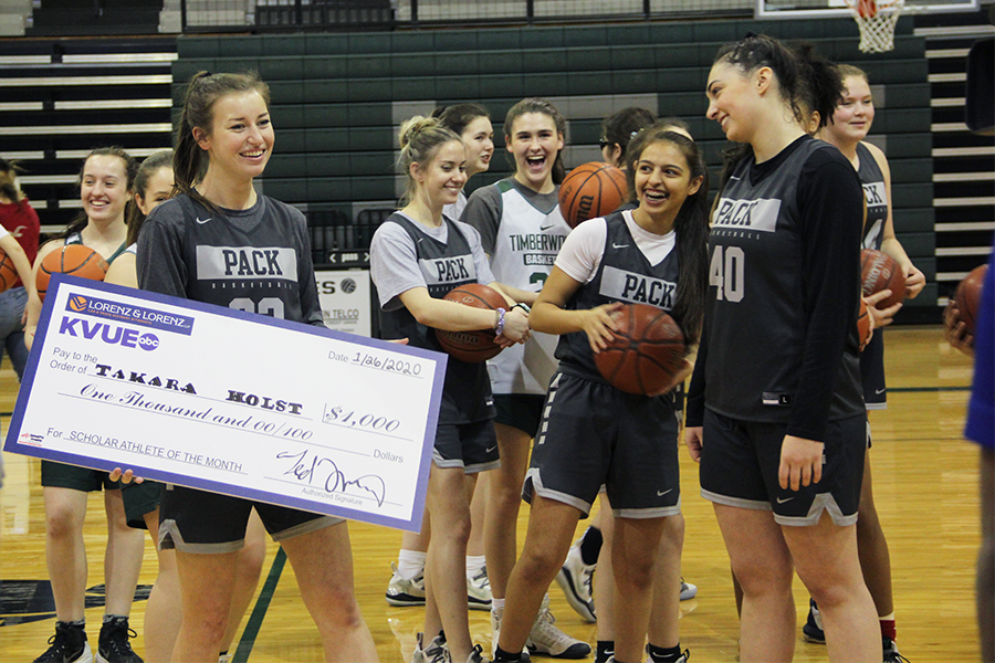 Walking+towards+her+family%2C+senior+varsity+basketball+captain%2C+Takara+Holst%2C+smiles+while+holding+her+scholarship+check+on+Jan.+23.+Holst+received+the+scholarship+as+part+of+the+KVUE+Scholar+Athlete+of+the+Month+Program.+%22I+was+in+complete+shock%2C%22+Takara+said.+%22The+fact+that+not+only+KVUE%2C+but+also+Ted+Lorenz+himself+came+to+grant+me+a+scholarship+was+just+amazing.%22
