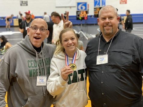 """Posing for a picture, senior varsity wrestler, Cassie King, stands with coaches Andrew Peterson and Beau Barksdale. King was awarded the regional champion medal on February 15, and according to her, her coaches and their attitudes are what helped her succeed. """"Their strive for being better than great is remarkable,"""" King said. """"They never eased up on me and always pushed me to be the absolute best. It was another standard that they expected me to achieve because they never wanted me to settle."""