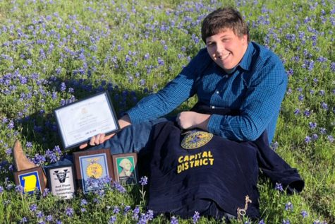 After competing in many competitions this year, senior Jeffrey Morphis poses with his awards from FFA. Morphis competed in multiple categories, including Entomology, Chapter Conducting, FFA Quiz and Swine Skillathon.