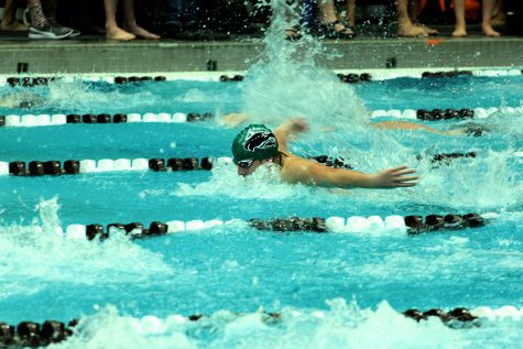 Pushing himself through the water, senior Kyle Blount swims the 100m Butterfly at Regionals at Texas A&M on Jan. 31. Blount used to be a soccer player, but changed his sport to swim after an injury.