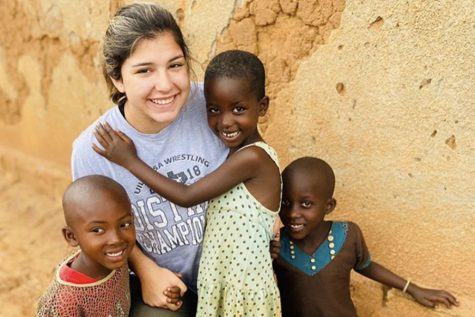 """Posing with two children on a mission trip to Rwanda, senior Faith Elliott grows her love of service and exploration. Elliott says what she values the most in her trips is the opportunity to spend time with children. """"I've never been particularly fond of kids but my heart bursts with love for those precious kids in Rwanda,"""" Elliott said. """"They've been through so much and they're still all filled with joy."""""""
