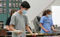 "Sophomore Kai Gray rehearses drumline show music while keeping in line with quarantine measures. Gray, and the rest of the percussion section, came back on Aug. 24. ""Once we're together playing music, I don't really pay attention to the masks or distancing, and things feel pretty normal,"" Gray said."