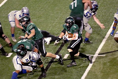 "Protecting the ball, senior RB Cade Haught looks for a hole during the Timberwolves 56-24 win over Georgetown on Friday. According to MaxPreps, Haught carried the ball nine times for 81 yards and three touchdowns. ""It was pretty surreal, but I was hyped and felt good to be a part of beating Georgetown,"" Haught said. ""My confidence grew more and more as I ran into that end zone every time."""