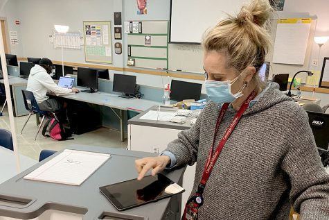 "During one of her classes, Mobile Maker teacher, Cheri Whalen, clicks through one of her iPads. In addition to 30 MacBook Pros, the Mobile Makers course also received 30 of the newest generation iPads. ""We had to use Macs because this program is being partnered with Apple,"" Whalen said."