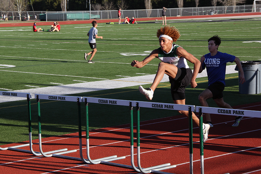 Looking ahead, junior Nick Grullon runs the hurdles at the track meet on Feb. 3. Due to Coronavirus.  the  amount of teams allowed at the meet were restricted, however the new changes don't deter his passion for track.
